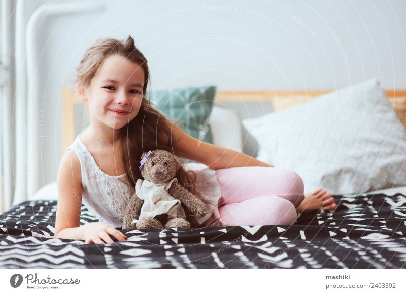 cute happy child girl relaxing at home on the bed Lifestyle Joy Relaxation Child Toys Teddy bear Smiling Sleep Dream Small Funny Cute Energy kid Wake up healthy
