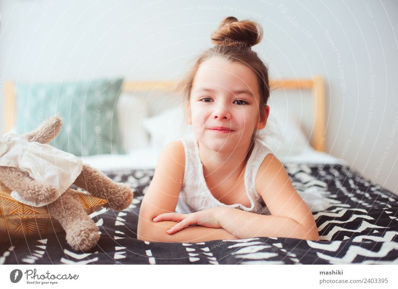 happy little child girl lying on her bed in the morning Lifestyle Joy Happy Hair and hairstyles Relaxation Sun Bedroom Child Toys Teddy bear Smiling Sleep Dream