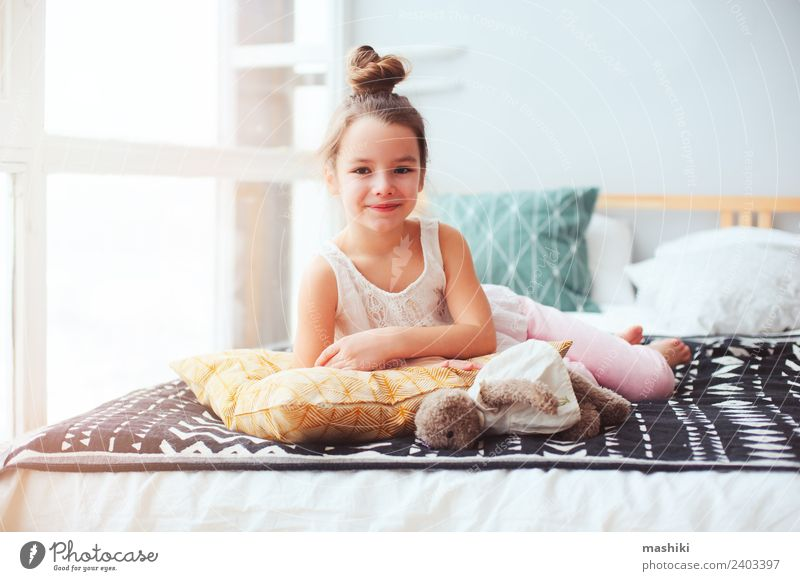 happy child girl wake up in the early morning Lifestyle Joy Relaxation Bedroom Child Smiling Sleep Small Funny Energy kid bed Wake up nursery Pillow healthy