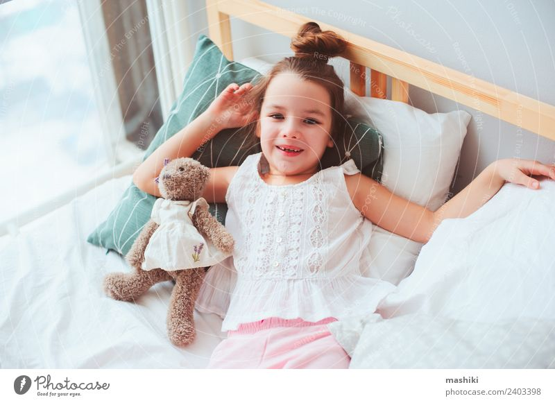 happy child girl wake up in the early morning Lifestyle Joy Happy Hair and hairstyles Relaxation Sun Bedroom Child Toys Teddy bear Smiling Sleep Dream Small