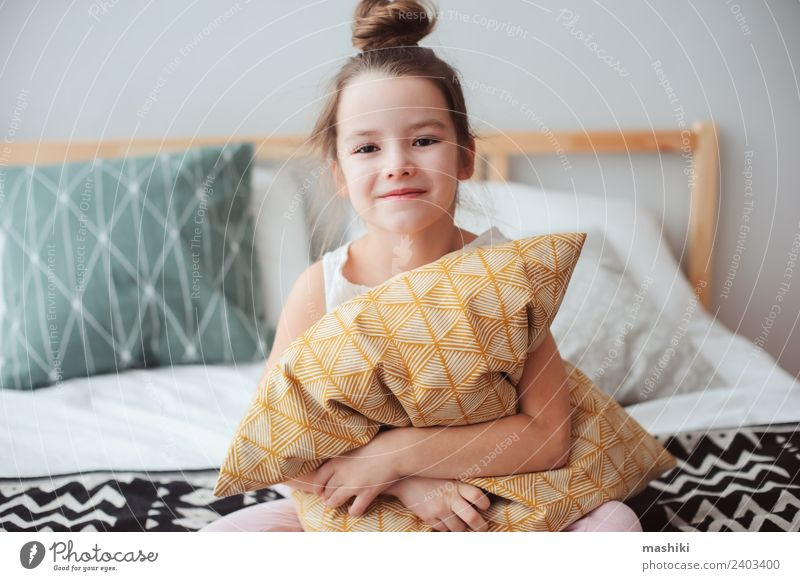 happy child girl sitting on bed and hugs pillow Child Relaxation Joy Lifestyle Funny Small Dream Smiling Energy Cute Sleep Bedclothes Home Bedroom Comfortable