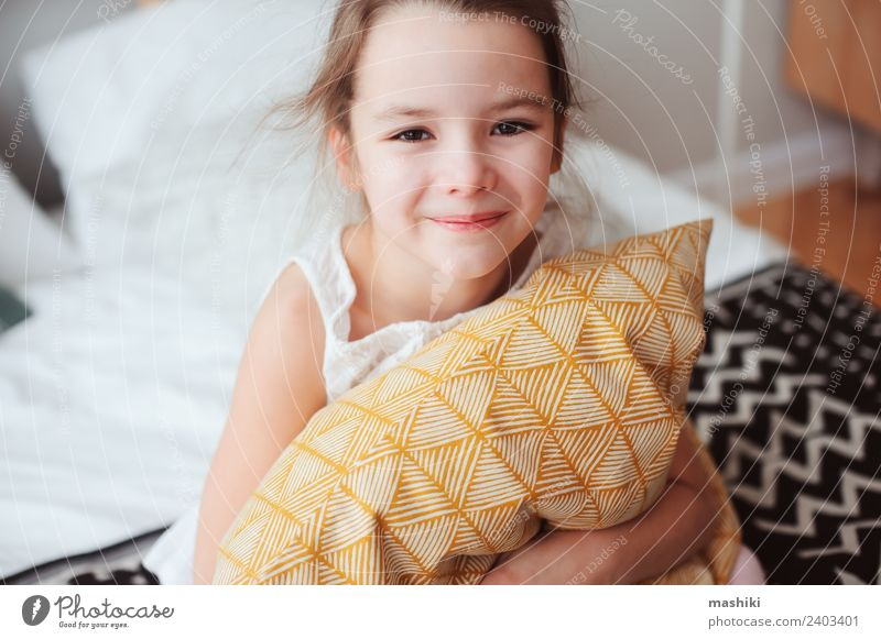 happy child girl sitting on bed and hugs pillow Lifestyle Joy Relaxation Sun Bedroom Child Toys Teddy bear Smiling Sleep Dream Small Funny Cute Comfortable