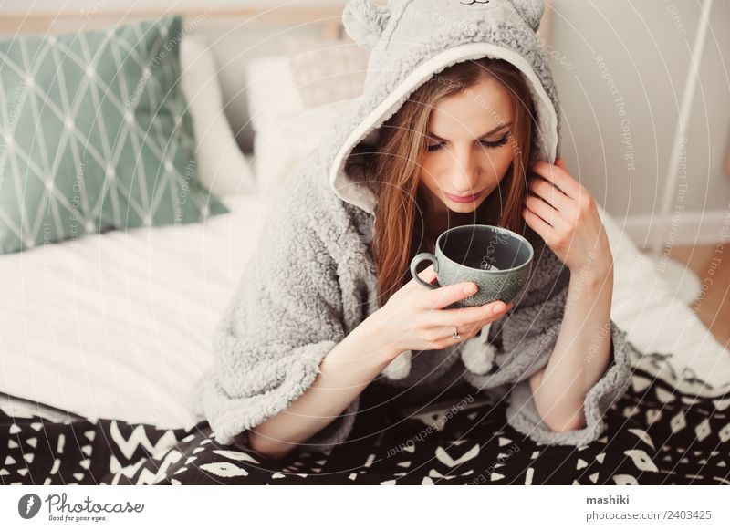 young beautiful woman relaxing at home on the bed Coffee Tea Lifestyle Relaxation Bedroom Woman Adults Culture Warmth Fashion Sit Dream Considerate Home Cozy