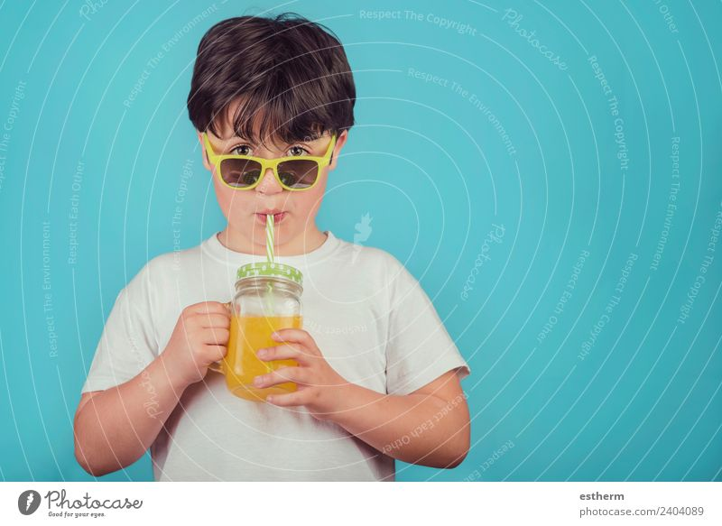 happy boy drinking orange juice on blue background Child Human being Joy Lifestyle Healthy Boy (child) Masculine Nutrition Infancy Smiling Curiosity To hold on