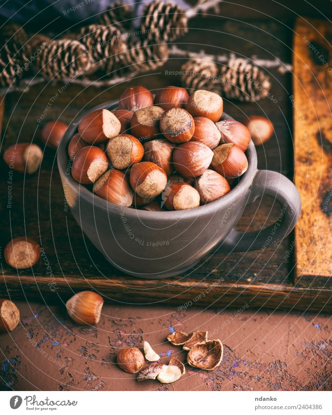 hazelnut in a shell Fruit Nutrition Vegetarian diet Plate Bowl Wood Eating Fresh Natural Above Brown background Organic food many seed Nutshell Tasty Snack