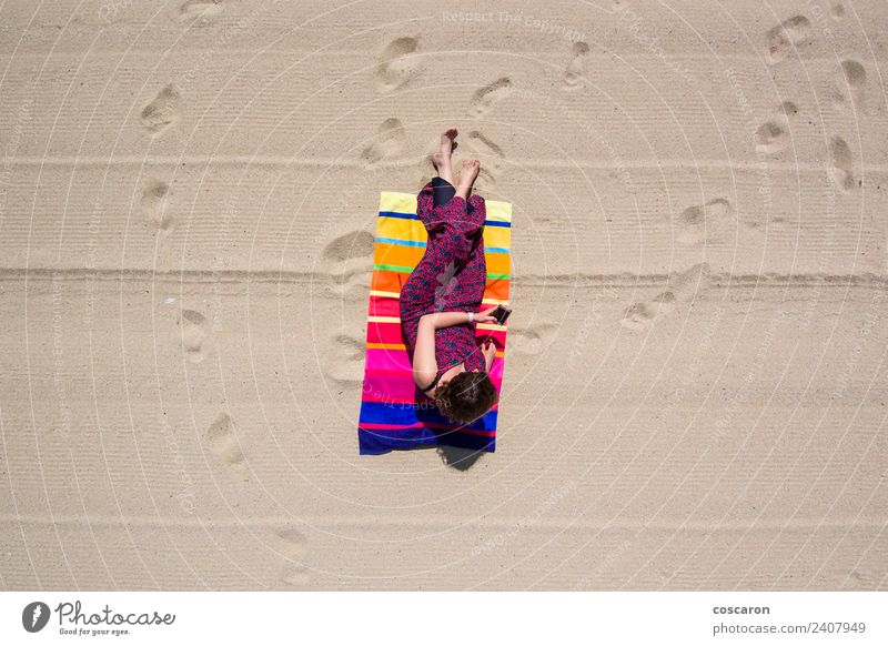 Woman in a towel on the beach looking at a mobile Lifestyle Elegant Joy Happy Beautiful Summer Sun Sunbathing Beach Ocean Telephone PDA Adults Nature Aircraft