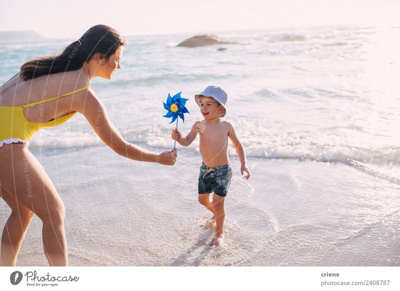caucasian mother and son playing with windmill at the beach Woman Child Summer Blue Sun White Ocean Joy Beach Adults Warmth Lifestyle Yellow Environment Coast