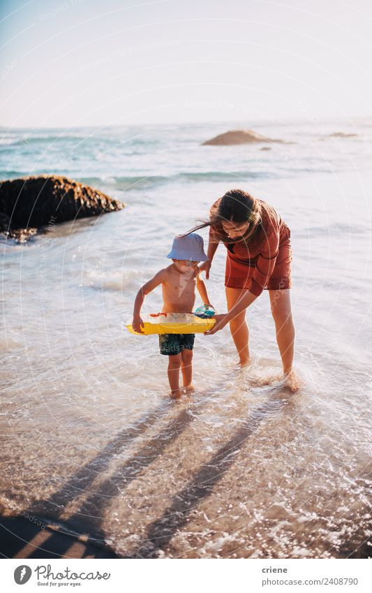 mother and son having fun with inflatable ring at beach Woman Child Sky Vacation & Travel Blue Sun White Hand Ocean Red Joy Beach Adults Lifestyle