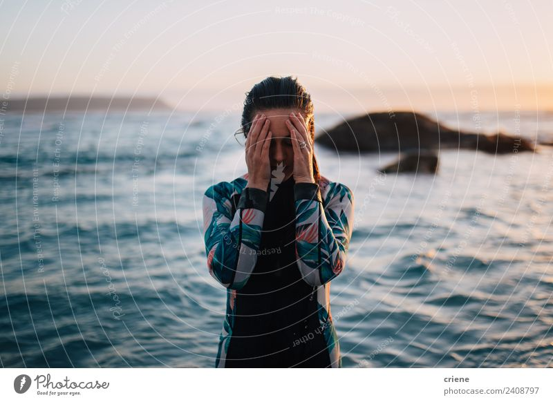caucasian woman in wetsuit by sunset Ocean Woman Adults Hand Rock Brunette Wet Blue Brown Surfing Wetsuit Sunset water young Caucasian hiding background