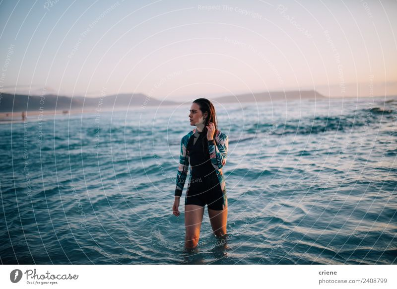caucasian woman walks out of water in wetsuit Beautiful Summer Sun Beach Ocean Sports Human being Woman Adults Nature Rock Brunette Think Dream Bright Long Wet