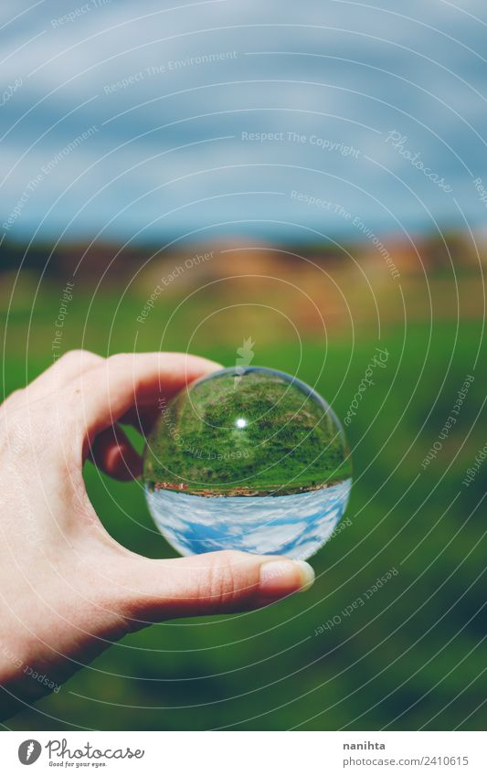 Beautiful and green landscape view through a crystal ball Hand Environment Nature Landscape Sky Spring Summer Beautiful weather Grass Field Crystal ball Glass