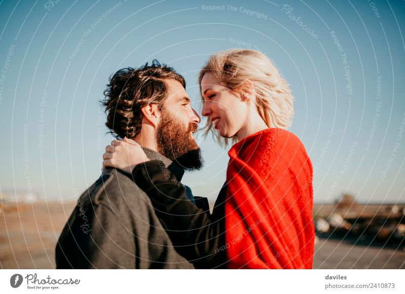 Bearded man and blonde woman looking to each. Lifestyle Joy Happy Beautiful Sun Winter Woman Adults Man Couple Fashion Blonde Kissing Smiling Love Embrace