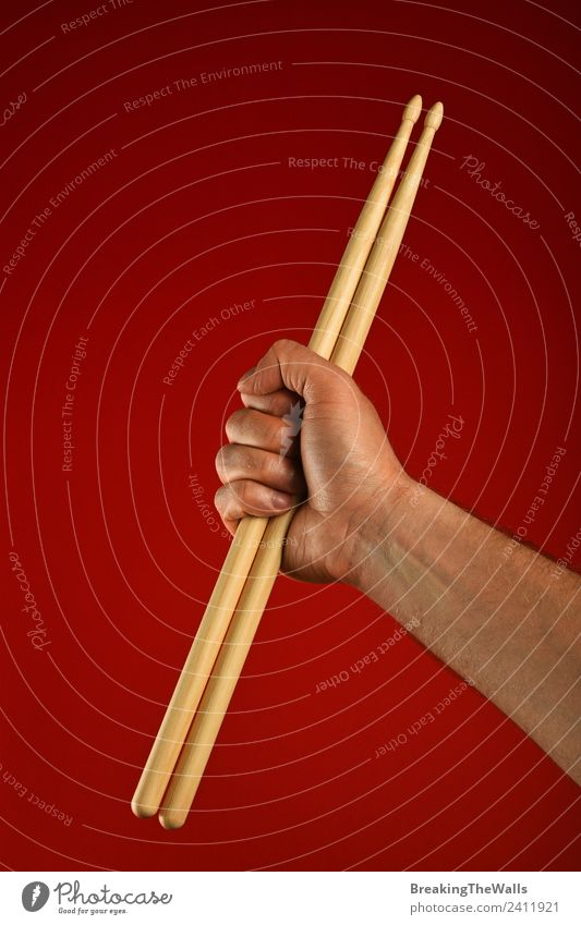 Man hand holding wooden drumsticks over red background Music Adults Hand 1 Human being Stage Shows Concert Musician Wood Red Fist Gesture Rocker Drummer Hold
