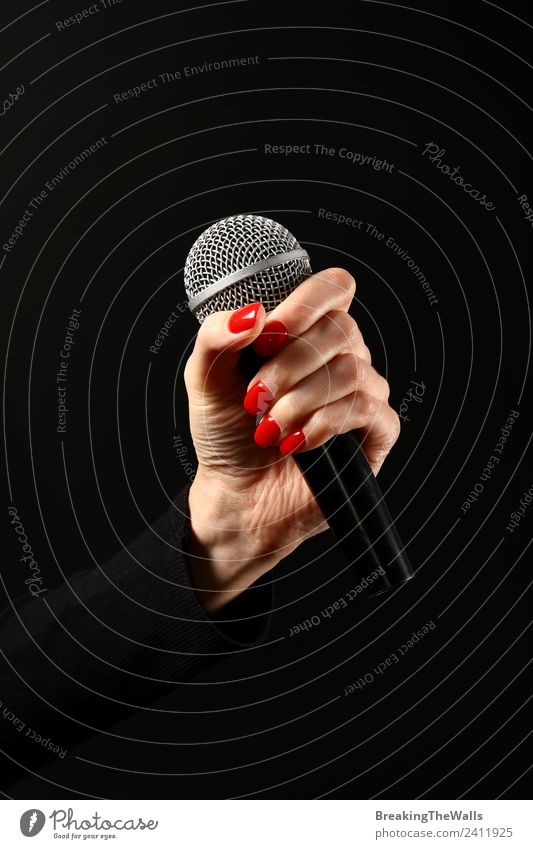 Woman hand holding microphone on black background - a
