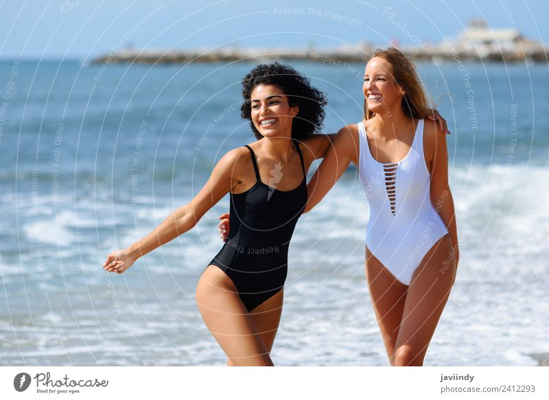 Two young women in swimwear on a tropical beach. Lifestyle Joy Happy Beautiful Hair and hairstyles Leisure and hobbies Vacation & Travel Tourism Summer Beach