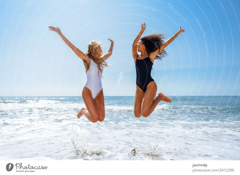Two women in swimwear jumping on a tropical beach Joy Vacation & Travel Tourism Summer Beach Feminine Young woman Youth (Young adults) Woman Adults Friendship