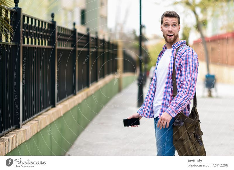Young bearded man surprised in urban background Human being Vacation & Travel Youth (Young adults) Man Young man Joy 18 - 30 years Street Adults Lifestyle Style