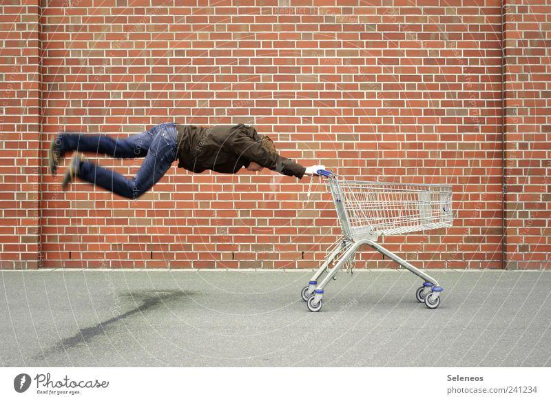 shopping frenzy Industry Trade Human being Masculine Man Adults 1 Places Wall (barrier) Wall (building) Street Jeans Brick Shopping Flying Speed Crazy Movement