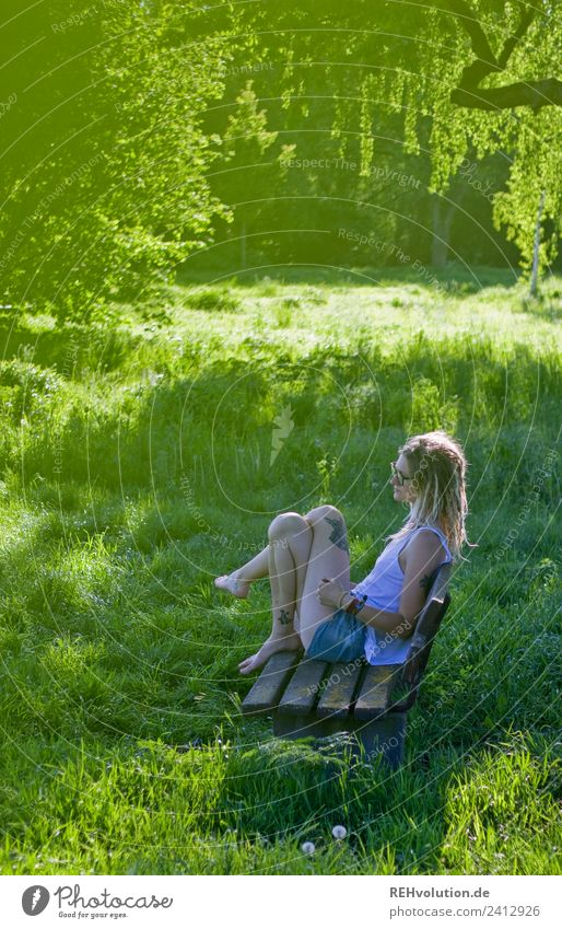 Jule Young woman with dreads is sitting on a bench in the green. Lifestyle Well-being Contentment Relaxation Calm Leisure and hobbies Human being Feminine
