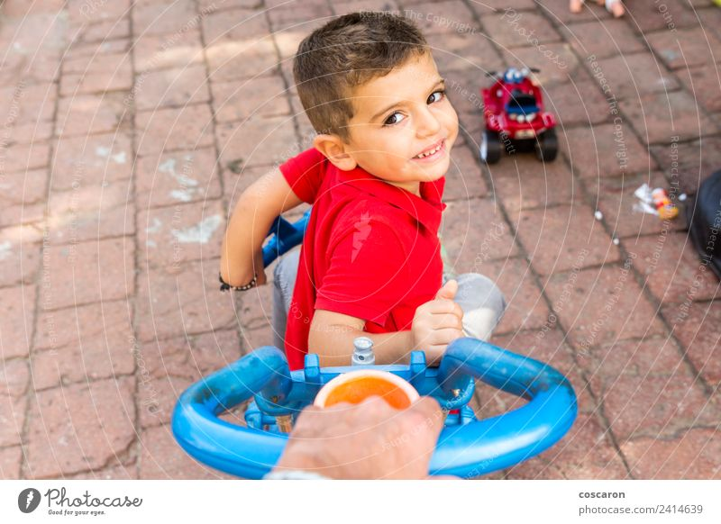 Father's hand pushing a child's tricycle Joy Playing Summer Garden Sports Child Boy (child) Parents Adults Family & Relations Hand Park Smiling Perspective