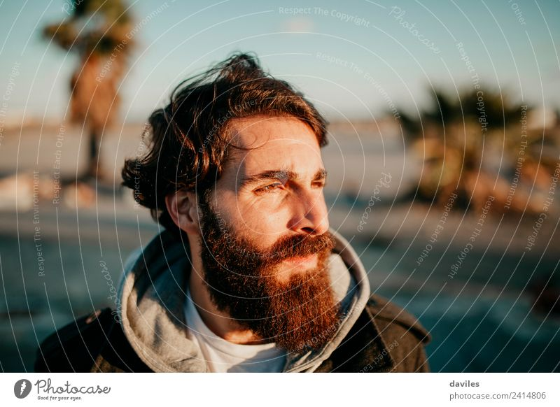 Man with dark hair and long beard posing at sunset with the sun light in his face. Lifestyle Face Calm Human being Masculine Young man Youth (Young adults)