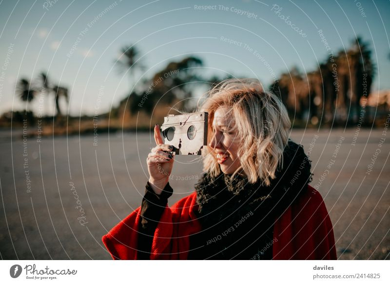Smiling blonde girl holding an old broken video tape in the hand and looking through the holes at sunset. Lifestyle Joy Sun Camera Technology Human being