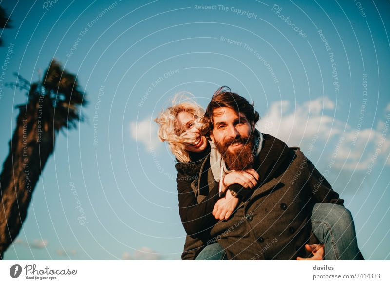 Bearded happy man carrying to her girlfriend in a piggyback way with blue sky in the background. Lifestyle Joy Leisure and hobbies Playing Human being