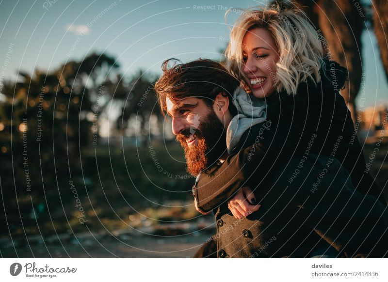 Smiling bearded man giving a piggy back to his girlfriend. Lifestyle Joy Leisure and hobbies Vacation & Travel Human being Young woman Youth (Young adults)