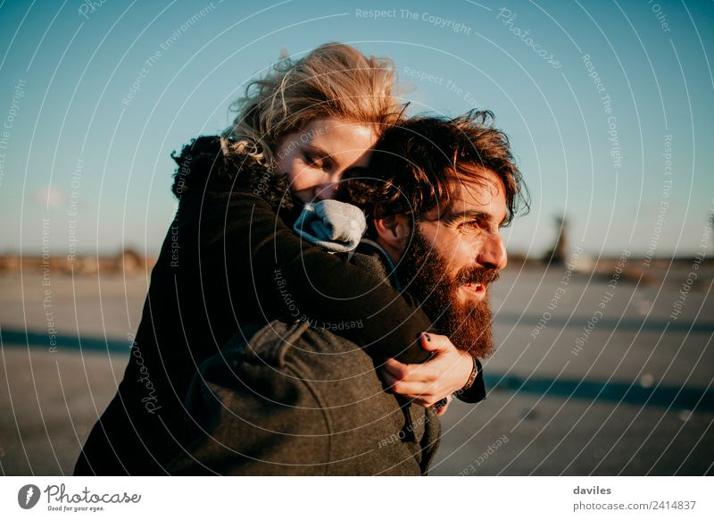 Bearded man carrying her girlfriend in a piggyback way outdoors at sunset. Lifestyle Joy Leisure and hobbies Human being Young woman Youth (Young adults)
