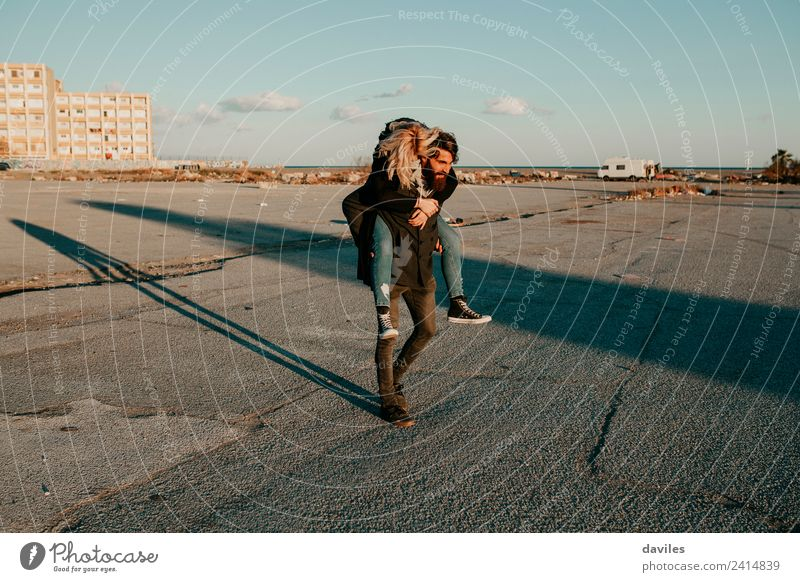 Man giving a piggy back to her girlfriend in a deserted city suburbs Lifestyle Joy Happy Playing Human being Young woman Youth (Young adults) Young man Woman