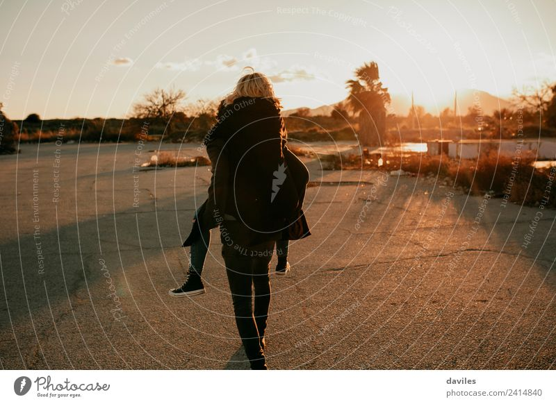 Man carrying in a piggyback way to his girlfriend on a deserted place at sunset. Lifestyle Playing Human being Young woman Youth (Young adults) Young man Couple