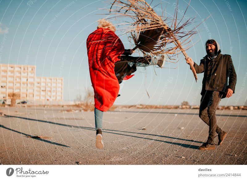 Cool woman and man playing and doing battles with plants and branches, outdoors at sunset. Lifestyle Joy Leisure and hobbies Playing Human being Young woman