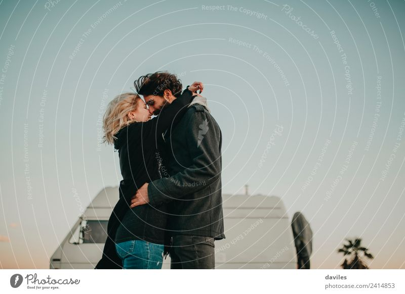 Blonde woman and bearded man embracing and smiling together with a van in the background at sunset. Lifestyle Joy Trip Camping Human being Young woman