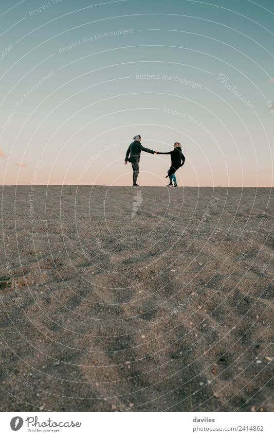 Lovely couple walking by the sand in the beach horizon. Lifestyle Joy Beautiful Beach Winter Human being Young woman Youth (Young adults) Young man Woman Adults