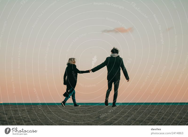 Cool couple walking by the hand at dusk Woman Human being Nature Vacation & Travel Youth (Young adults) Man Beautiful Ocean Joy Winter Beach 18 - 30 years