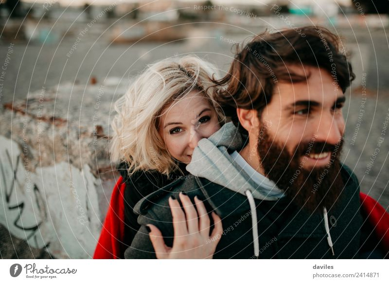 Blonde girl looks at camera while embraces her bearded boyfriend. Lifestyle Leisure and hobbies Human being Young woman Youth (Young adults) Young man Woman