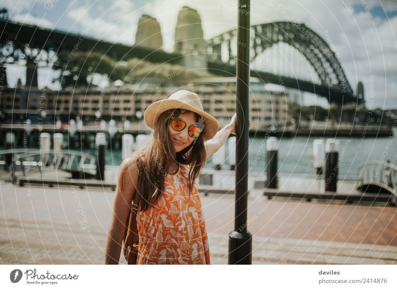 Cute girl with hat and sunglasses posing in Sydney city, with Harbour Bridge in the background, Australia. Lifestyle Vacation & Travel Trip City trip