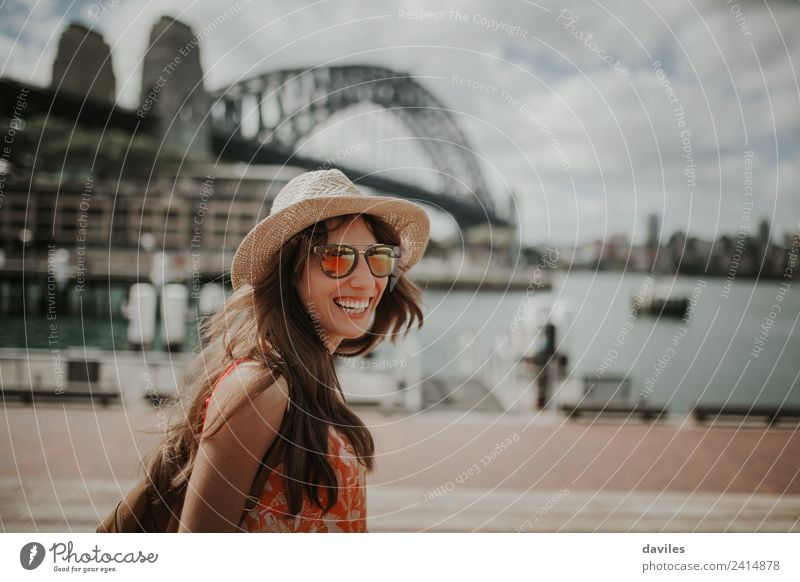 Happy blonde woman with hat and sunglasses laughing in Sydney city Harbour, with Harbour Bridge in the background, in Australia. Lifestyle Style Joy