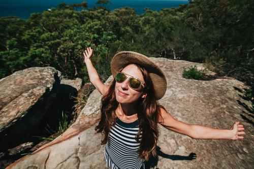Happy white woman with opened arms breathing and enjoying the sun in the Australian forest. Lifestyle Joy Beautiful Wellness Leisure and hobbies