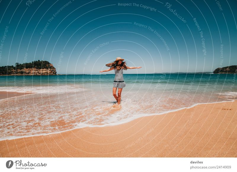 Woman with a hat and a dress dancing in the beach water in a beautiful Australian beach. Lifestyle Joy Wellness Well-being Freedom Adults 1 Human being