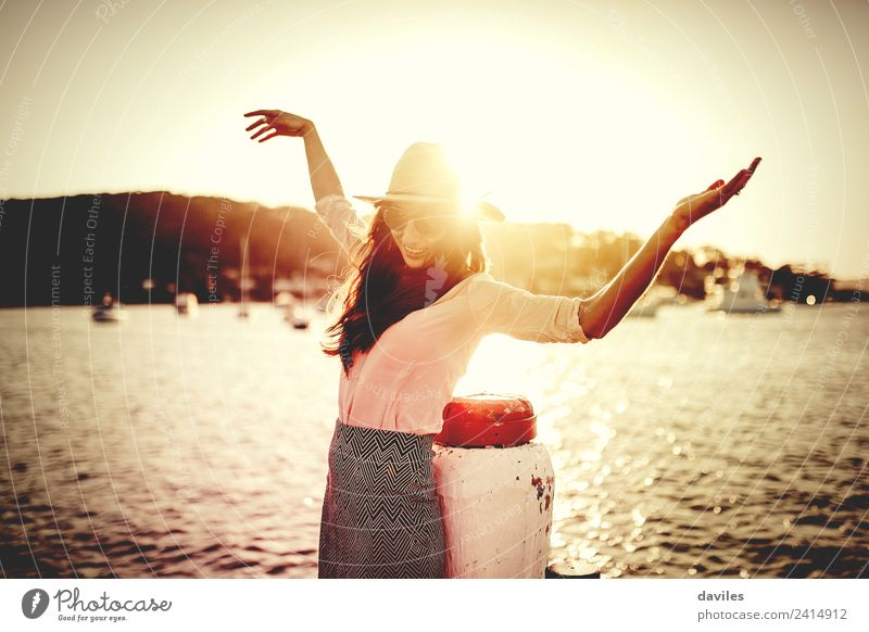 Smiling woman with sunglasses and hat raising arms happy with the sea in the background. Lifestyle Elegant Style Well-being Vacation & Travel Sun Beach Ocean
