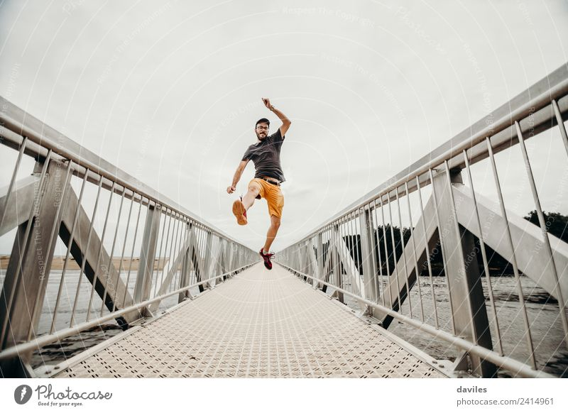 White man with shorts and t shirt jumping with energy on a bridge. Lifestyle Athletic Wellness Well-being Leisure and hobbies Vacation & Travel Adventure