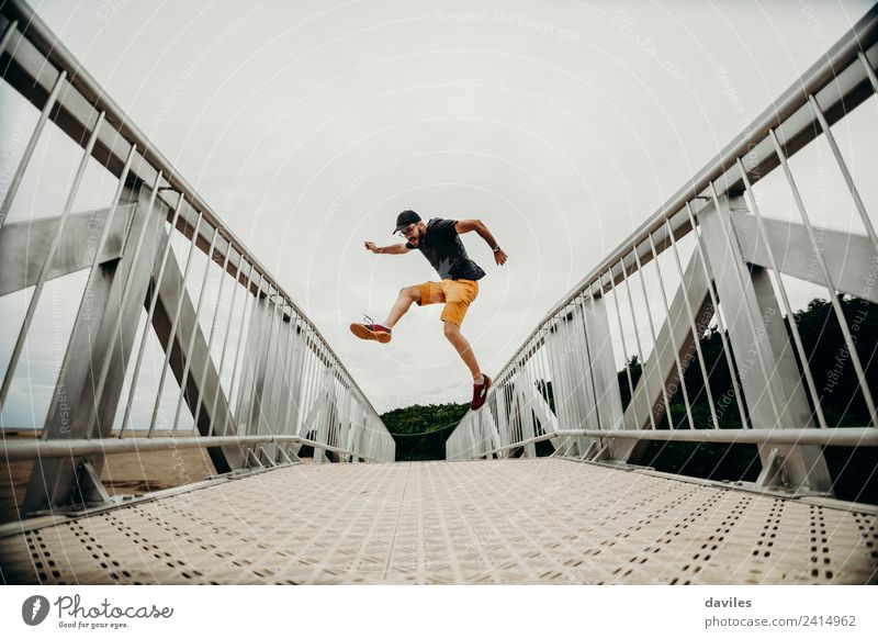 Man jumping on a bridge Human being Nature Vacation & Travel Youth (Young adults) Joy 18 - 30 years Adults Lifestyle Yellow Environment Freedom Orange Trip Jump