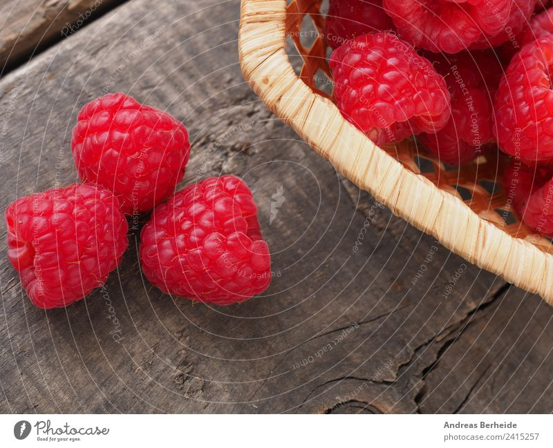 Organic raspberries on a wooden table Fruit Dessert Organic produce Vegetarian diet Style Healthy Eating Summer Garden Nature Delicious natural raw red ripe