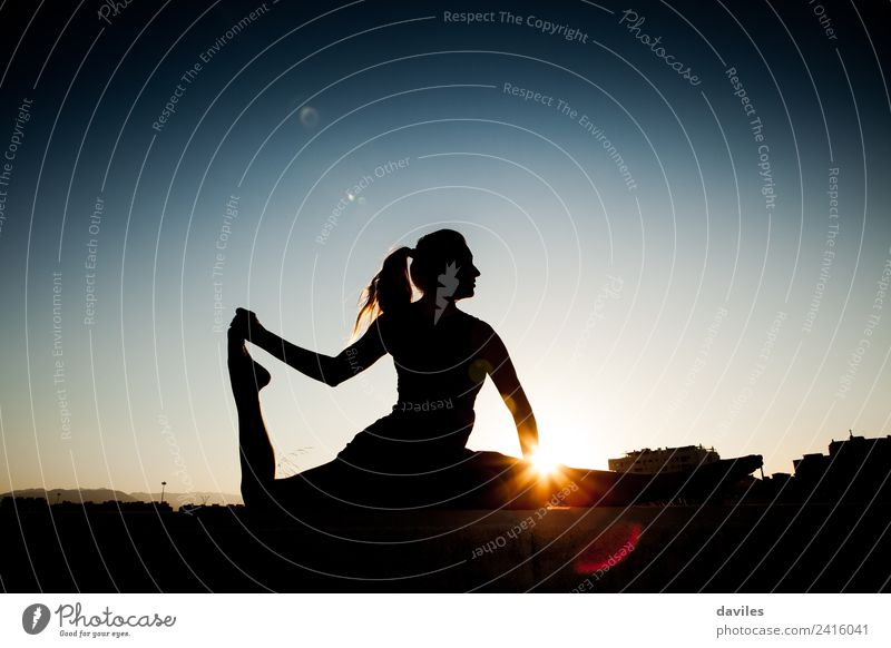 Woman silhouette during stretching session after fitness session. Backlight during sunset. Lifestyle Body Fitness Wellness Well-being Relaxation