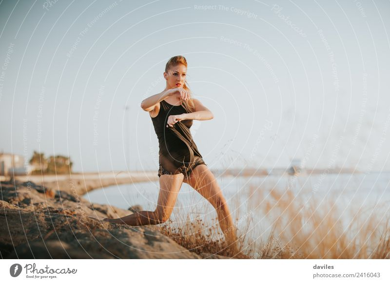 Blonde white woman performing contemporary dance at the sea shore. Lifestyle Joy Athletic Fitness Sports Training Human being Feminine Young woman