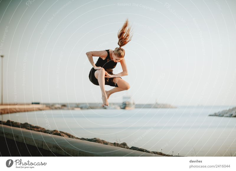 Blonde woman jumping in the air Lifestyle Joy Leisure and hobbies Handcrafts Vacation & Travel Sun Ocean Dance Sports Human being Feminine Young woman