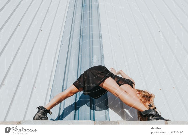 Blonde dancer in black dress against industrial wall. Lifestyle Elegant Beautiful Relaxation Dance Sports Human being Woman Adults 1 18 - 30 years