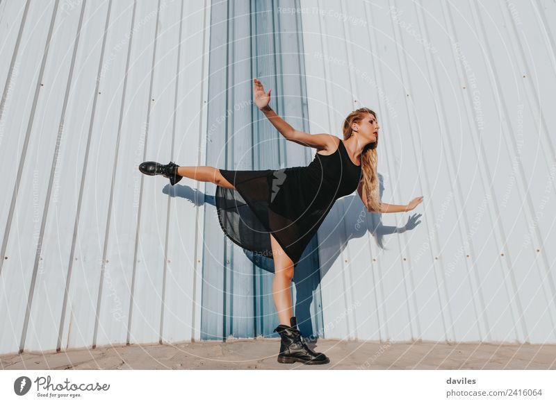 Blonde woman in black dress dancing while raises a leg up. Lifestyle Body Dance Sports Human being Feminine Woman Adults Youth (Young adults) Arm 1