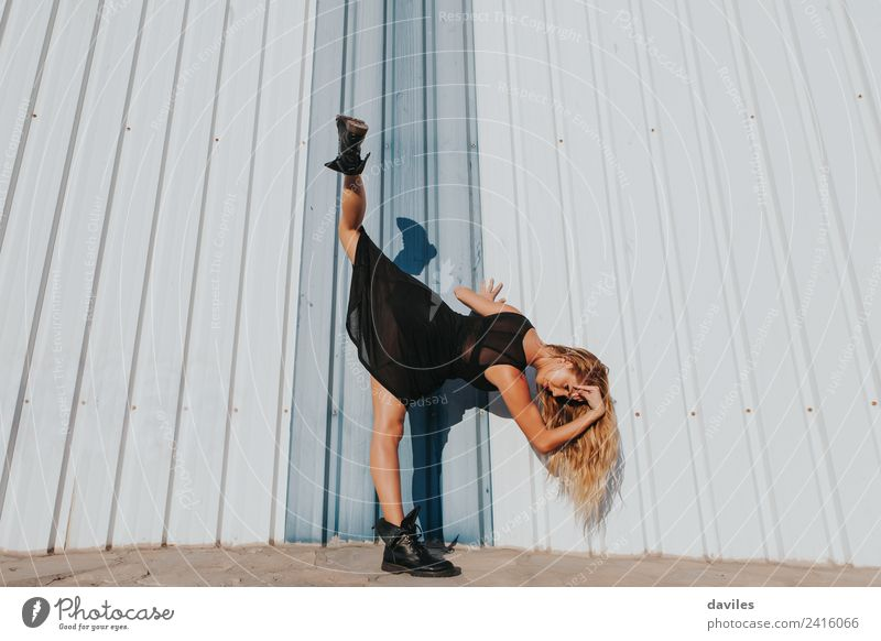 Blonde woman performing contemporary dance, raising up a leg, against a wall. Lifestyle Elegant Style Exotic Sports Human being Woman Adults